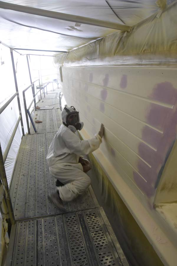 A worker preparing the boat to be painted